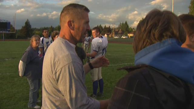 A Bremerton high school football coach prays on the field, despite a district investigation into his post-game prayer ritual.